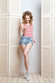 pic of jalousie  - Young beautiful woman wearing jeans shorts and  top posing in front of a jalousie - JPG