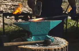 picture of anvil  - Blacksmith forges iron on anvil - JPG
