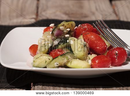 Cucumber, tomato, feta cheese and dill salad with a vinaigrette dressing on a white plate with a fork at mealtime.