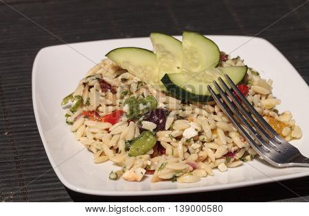 Greek orzo salad with cucumbers, sundried tomatoes, olives, onions, peppers and feta cheese on a white plate with a silver fork.