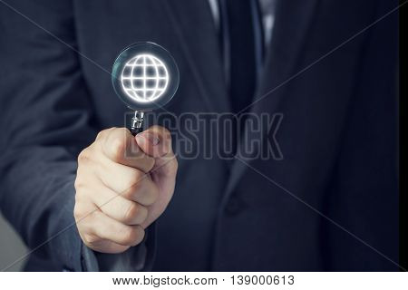 Businessman In Suit Looking For Virtual World Using A Small Magnifier