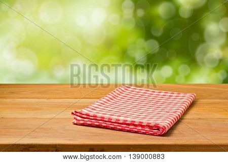 Beautiful background with empty wooden table and tablecloth over bokeh garden. Picnic table. Ready for product montage.