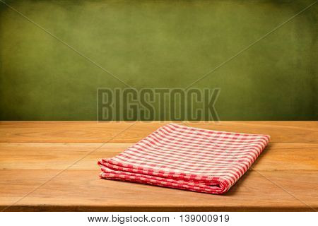 Empty wooden table with checked tablecloth over grunge green wall. Ready for product montage