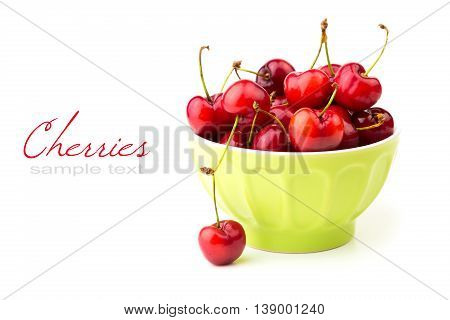Red cherries in bowl on white background