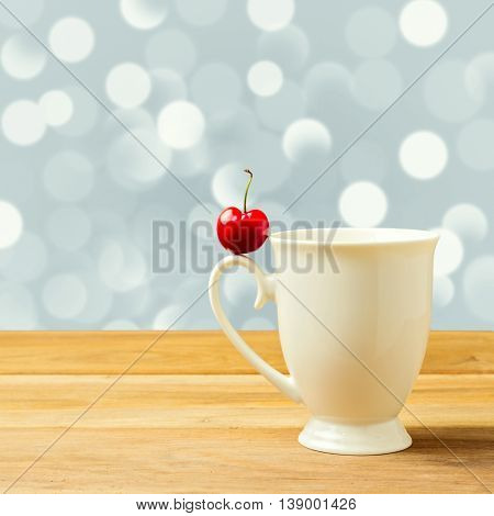 Single cherry on cup handle over bokeh background