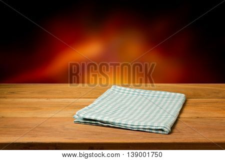 Empty wooden table with checked tablecloth over blur fire background. Perfect for product montage.