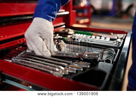 Close-up image of mechanic taking wrench from the box
