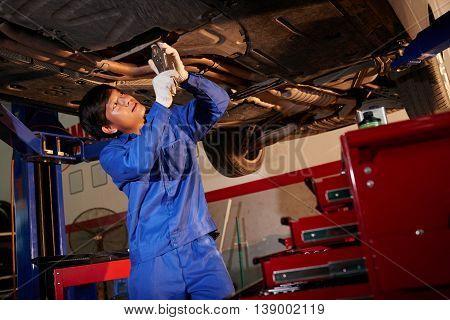 Vietnamese mechanic examining lifted car in garage