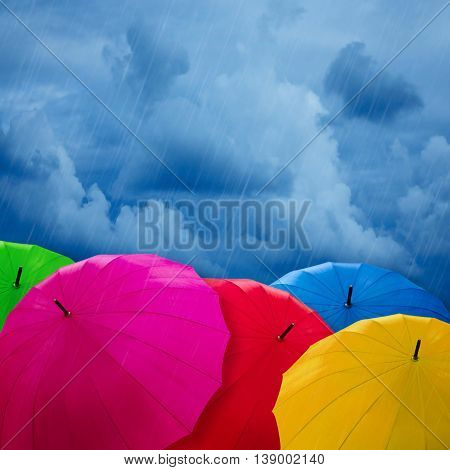 Colorful umbrellas over cloudy sky. Bad weather concept