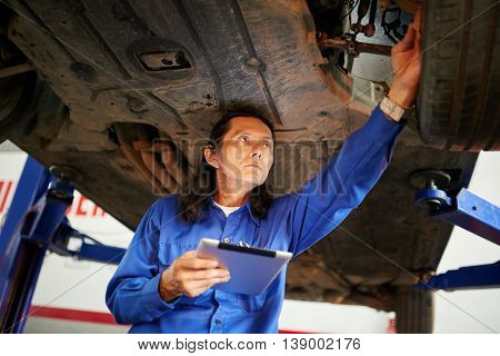 Mechanic using tablet computer when checking car