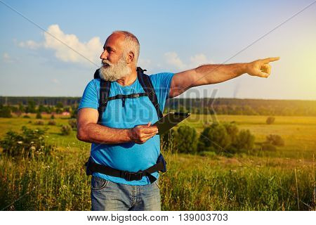 Bearded fit aged man with rucksack is holding a data tablet in his hand and pointing at something in the field his head turned in opposite direction