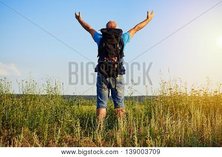 Back view of aged man in casual clothes with rucksack standing in the grass with hands lifted enjoying the beauty of nature