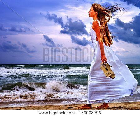 Summer girl sea. Bare foot girl goes on sea coast. Beautiful sea landscape.