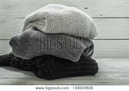 warm knitted sweater three pieces blackgrey and white on a wooden white background closeup