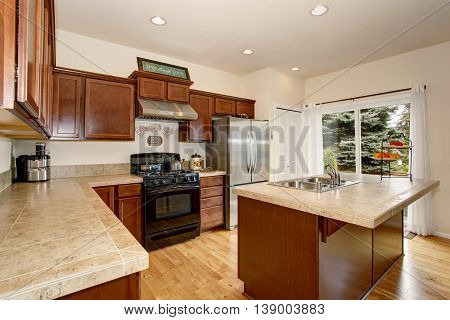 Cozy Kitchen Room With Tile Counter Top, Kitchen Island And Stainless Steel Fridge