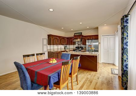 Bright Kitchen And Dining Room Interior With White Walls And Hardwood Floor.