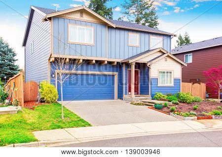 Nice Curb Appeal Of Blue House With Front Garden And Garage With Driveway