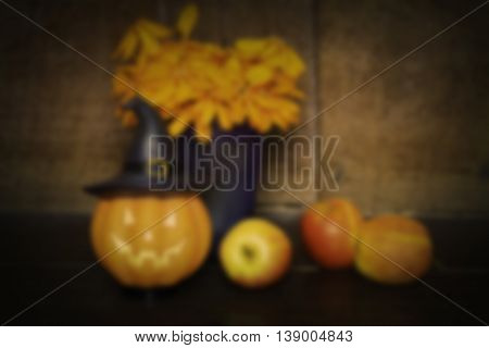 halloween set de-focused pumpkin doll and apple on wooden background black vignette