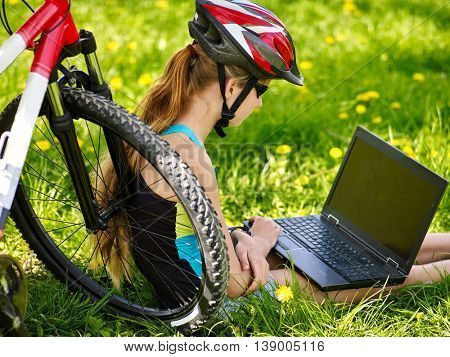 Bikes cycling girl. Girl rides bicycle. Girl in cycling sitting near bicycle and watch laptop. Cycling is good for health. Bicyclist wearing helmet.