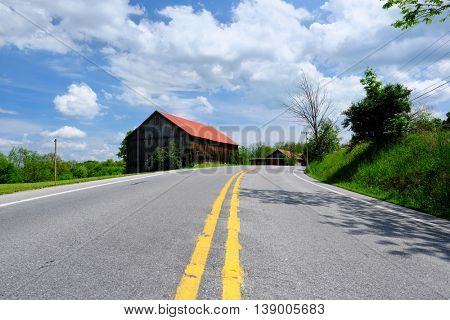 Old red roof barn near highway in Pennsylvania at sunny summer day