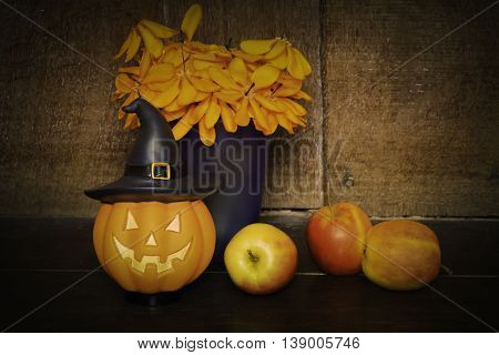 halloween set pumpkin doll and apple on wooden background black vignette