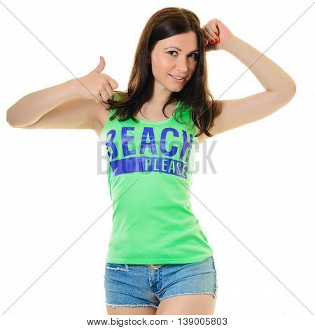 Slim brunette in a green T-shirt and denim shorts is raising thumb up. the inscription on the t-shirt - the beach please