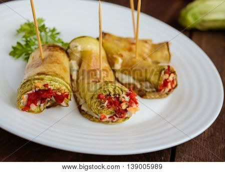 Sharp rolls zucchini stuffed with garlic herbs and chili peppers on a white plate. Close-up