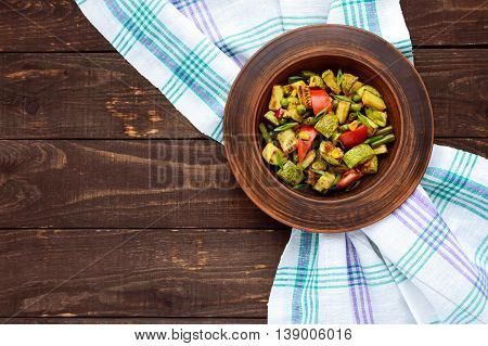 Dietary vegetarian salad with grilled zucchini fresh tomatoes sweet corn and herbs in a clay bowl on dark wooden background.