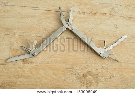 A multifunction tool isolated on a wooden background