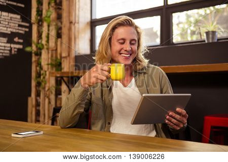 Happy young man using digital tablet while having coffee in cafeteria