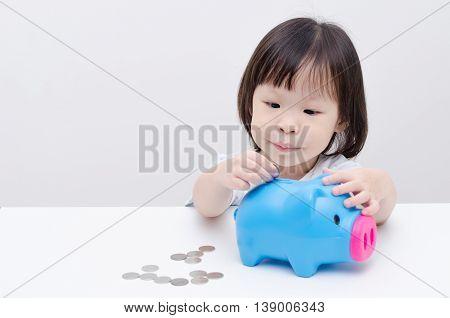 Little Asian girl insert coin into piggy bank
