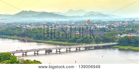 Hue, Vietnam - June 21st, 2015: Bridge connects both sides Perfume River beautiful, distant flag flying in port Hue Citadel, horizon Ngu Binh Mountain scenery makes this place very poetic, idyllic