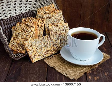 Dietary crunchy cracker with cereals (sunflower seeds flax and sesame) and a cup of tea on a dark wooden background.