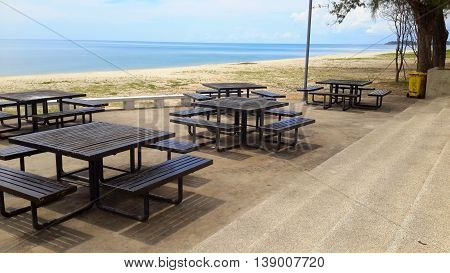 looking down steps at five dark brown wooden picnic tables  with benches at little plaza area on Samila Beach, Thailand