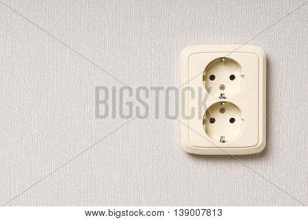 White electric socket on the wall with space for text.  Close up.