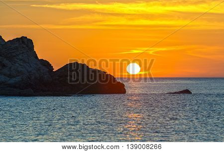 Sunrise over the bay with rocks protruding path toward the sun was jutting out of the water gradually making yellow skies welcomed the new day of peace and beautiful
