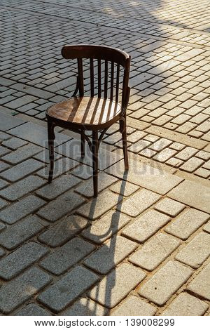 Old Viennese chair on the cobbles in the ray of setting sun