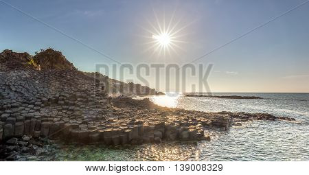 Morning sun on Giant Causeway when sunstar shining down on bay radiating stone is recognized as a national landmark, this place attracts tourists to relax and explore