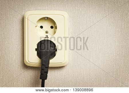 Electrical socket with connection sockets on a gray wall with space for text