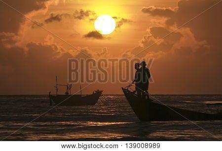 Khanh Hoa, Vietnam, February 15th, 2013: Fishermen fishing at dawn when the sun beautiful waters rising from water it's great to watching the beautiful waters of Khanh Hoa, Vietnam