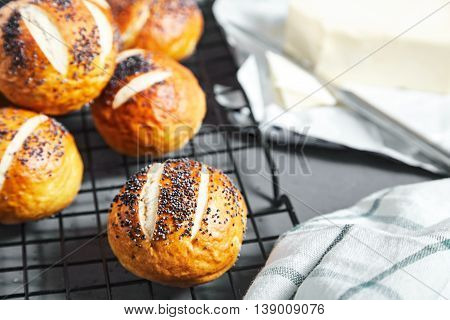 Group of homemade baked golden pretzel buns with poppy seeds and butter near it on stone background. Pretzel bun is german cuisine dish, ideal for lunch or breakfest with butter and tea.