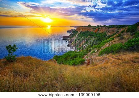 Dramatic sunset at cape Fiolent with bush and grass at foreground. Crimea
