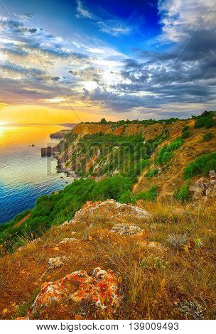 Dramatic sunset at cape Fiolent with rocks and grass at foreground. Crimea
