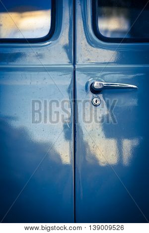 Closeup of locked blue oldtimer car back door with windows, lock and door handle in mysterious vintage light with reflections on it