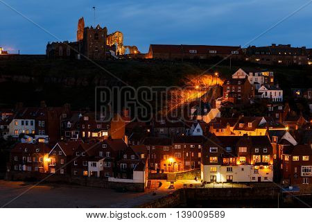 WHITBY ENGLAND - JULY 16: Whitby Abbey with harbour in foreground at night. In Whitby North Yorkshire England. On 16th July 2016.