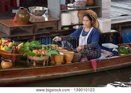 BANGKOKTHAILAND - FEBRUARY 14 2016: Unidentified thai woman in Taling Chan Floating Market . Featuring many small boats laden with colourful fruits vegetables and Thai cuisine.