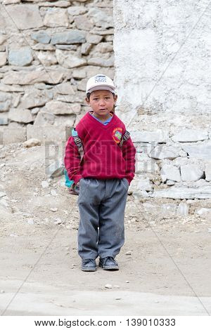 LAMAYURU INDIA - JUNE 16 2015: Unidentified young boy going home from school after lessons at the local school at Lamayuru Gompa Ladakh North India