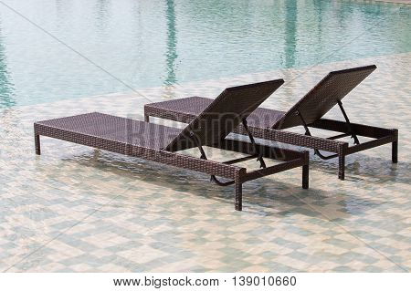Two deck chairs in the swimming pool at a tropical resort