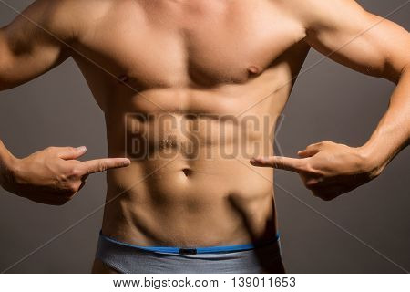 male bare muscular torso with six packs on strong body showing on belly with fingers in studio on grey background