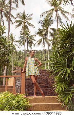 Young slender woman in a tropical garden on a background of palm trees and plants.